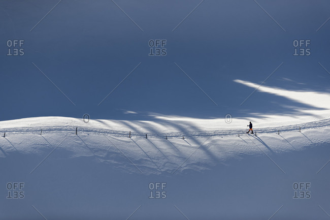 Distant view shot of single person walking along path in snow, Gingins, Vaud Canton, Switzerland