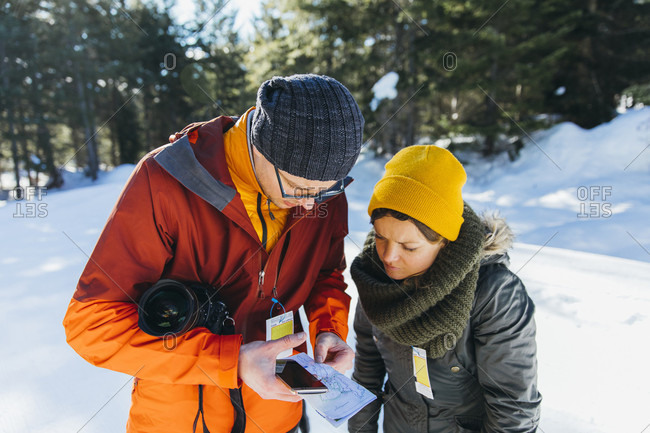 Waist up shot of man and woman checking map while hiking in winter, Whistler, British Columbia, Canada