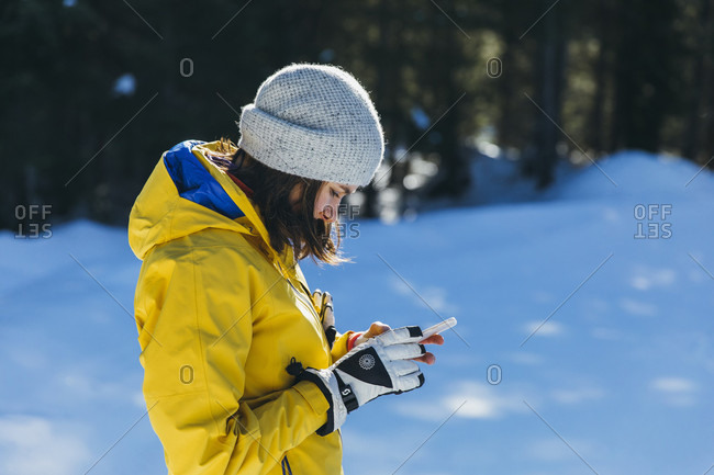 January 31, 2017: Side view shot of young woman using phone outdoors in winter, Whistler, British Columbia, Canada