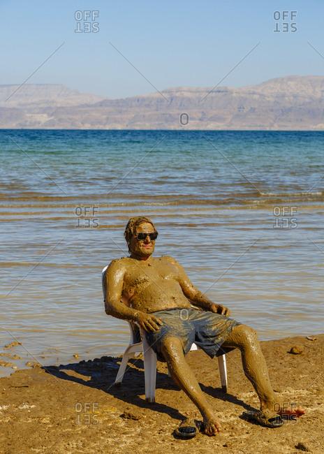 Ein Gedi, Israel - October 11, 2017: Man covered with mud at the Ein Gedi beach, Dead Sea, Israel