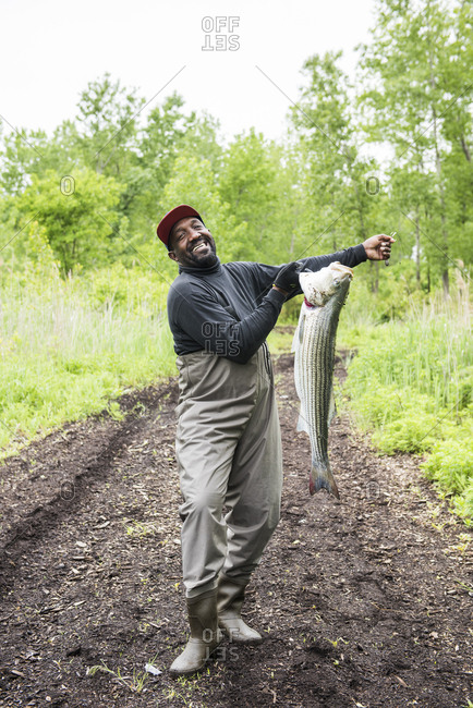 Far Rockaway, Queens, NY, USA - May 27, 2018: Man proud of the Striped Bass he caught
