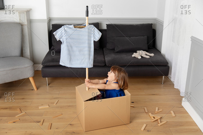 Little girl playing pretend in a box