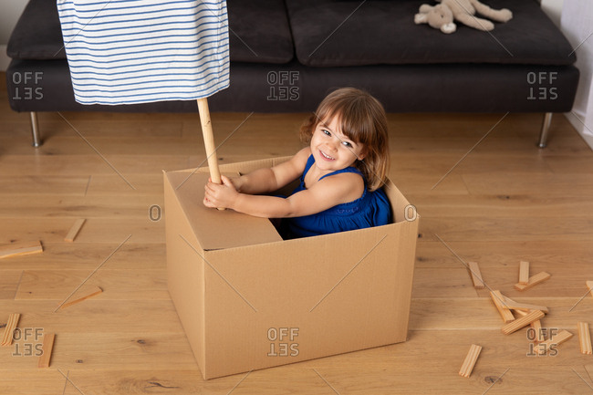 Little girl playing pretend in a cardboard box