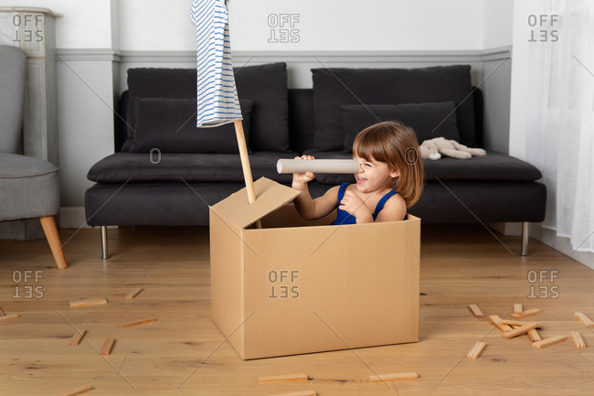 Little girl looking through cardboard paper roll while playing pretend in a box