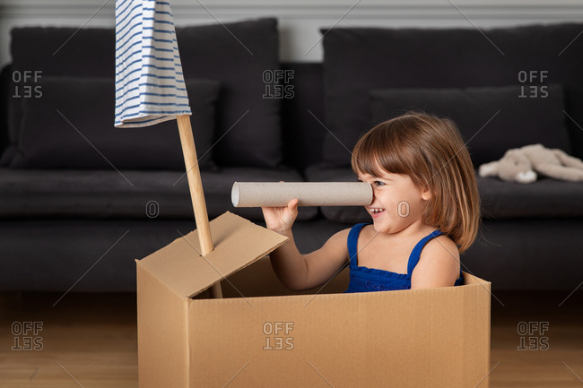 Little girl having fun with a cardboard paper roll while playing pretend in a box