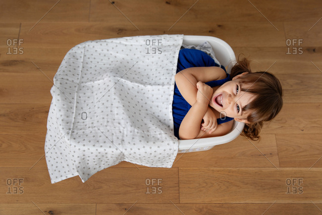 Little girl playing pretend in a basket of laundry