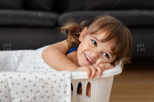 Girl pretending a basket of laundry is her bed