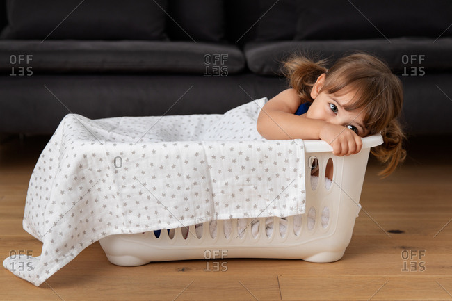 Girl playing pretend in a basket of laundry