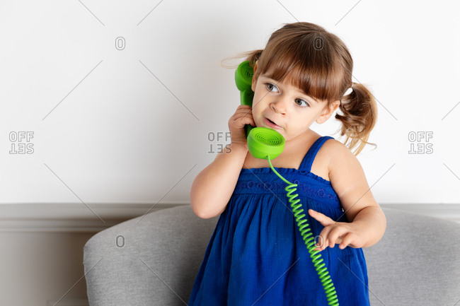 Little girl talking on play green corded phone