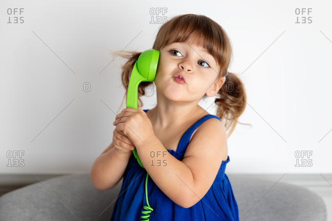 Little girl making kissy face while talking on play green corded phone