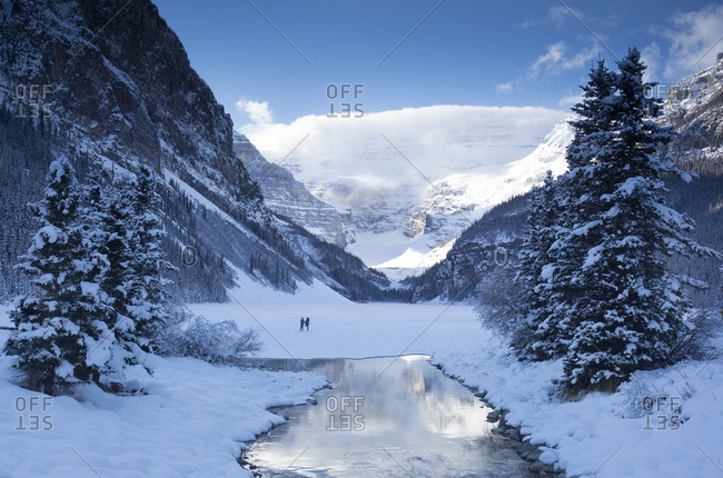 Tourist enjoying majestic view of Lake Louise in Banff National Park in the winter