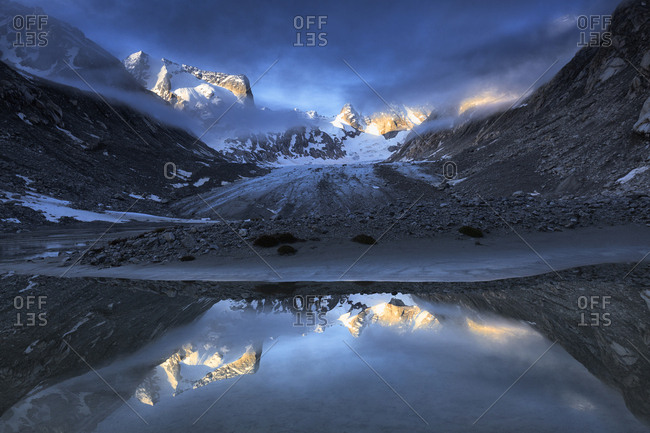 Forno Glacier reflected in a pond at foggy sunrise, Forno Valley, Maloja Pass, Engadine, Graubunden, Switzerland, Europe
