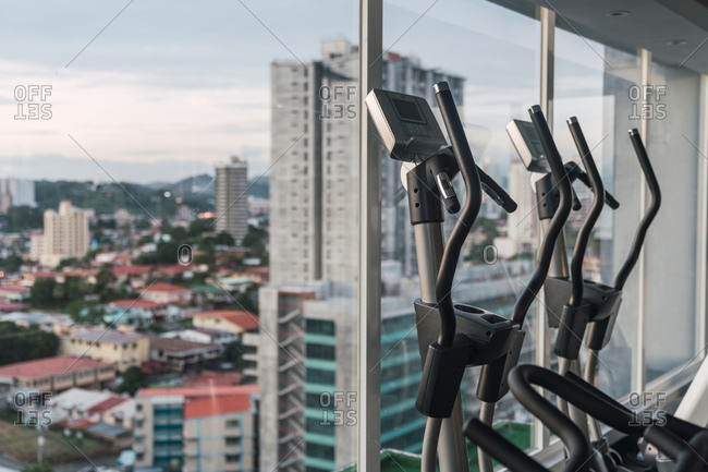 Interior shot of fitness machines in row inside of contemporary gym with windows and cityscape