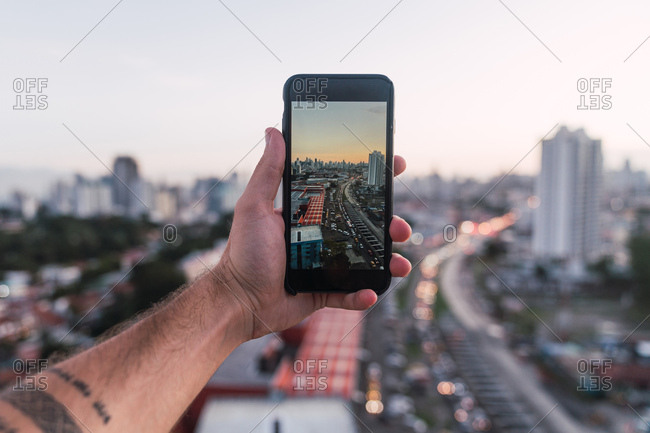 Crop male hand holding smartphone with picture of cityscape in sunset time