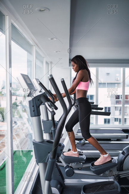 Side view of skinny black woman working out on elliptical trainer in modern gym of Panama city