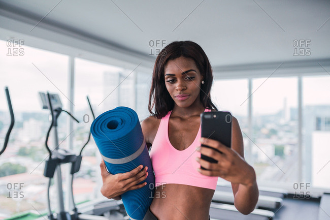 Modern skinny ethnic sportswoman holding rolled yoga mat and taking selfie in gym