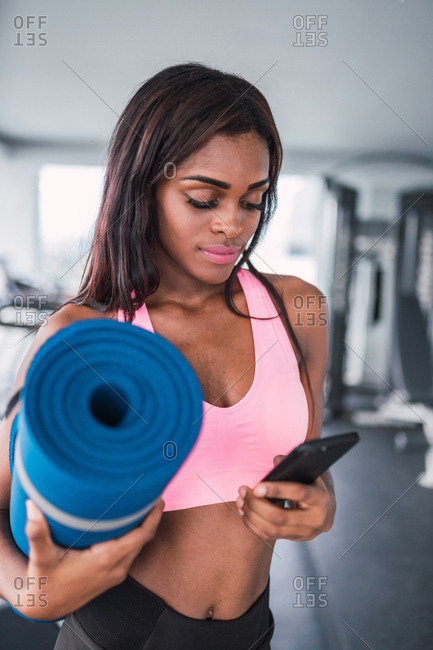 Pretty black woman surfing phone while standing in gym with rolled yoga mat in hands