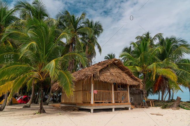 Exterior of small bungalow with thatched roof on sandy beach among green palms, Panama