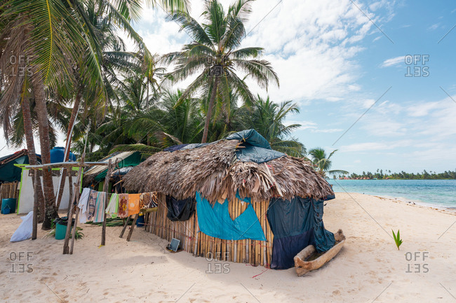 Exterior of living residential thatched hut on sandy beach of tropical island, Panama