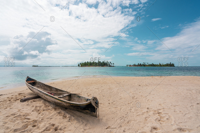 Picturesque landscape of wooden aged boat on sandy beach of tropical ocean shoreline, Panama