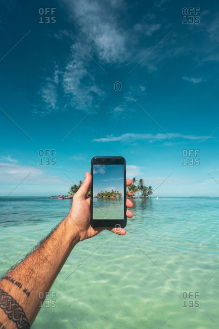 Crop male hand with phone taking picture of beautiful green island in ocean, Panama