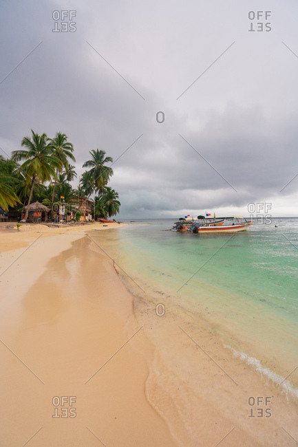 Landscape with green palm trees on remote sandy beach with boats floating in turquoise water in clouds, Panama