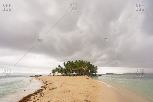 View of shallow sandy beach with green palms in overcast clouds, Panama