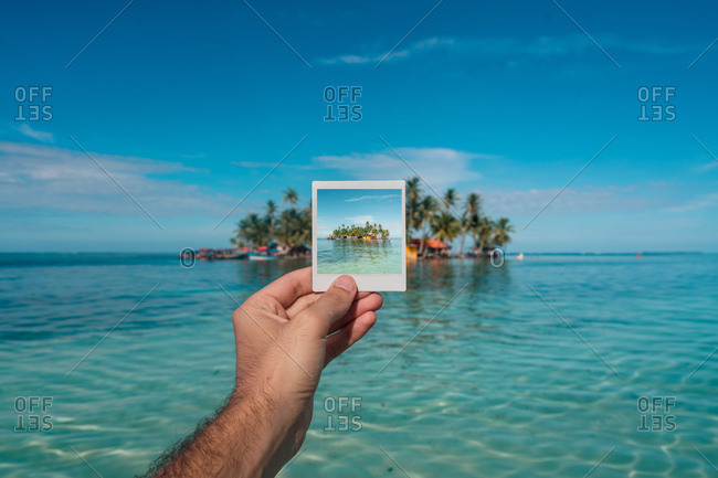 Crop hand of traveling man with instant picture of remote island on background of tropical landscape in ocean, Panama