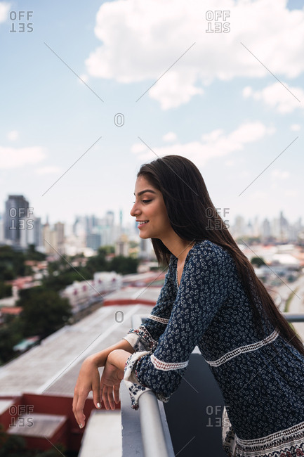 Side view of charming young woman in beautiful dress smiling and leaning on terrace railing on blurred background of Panama City on cloudy day