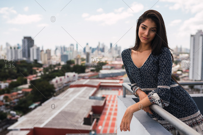 Attractive young woman in lovely dress leaning on terrace railing on blurred background of majestic Panama City on cloudy day