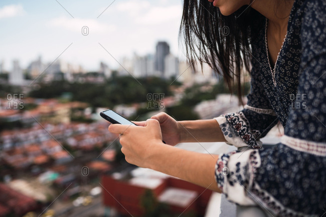 Unrecognizable female standing on terrace and browsing smartphone on blurred background of Panama City