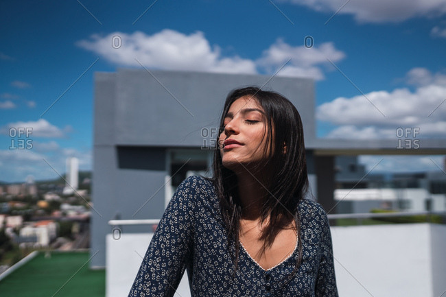 Attractive young female keeping eyes closed and enjoying weather while standing on terrace on wonderful cloudy day