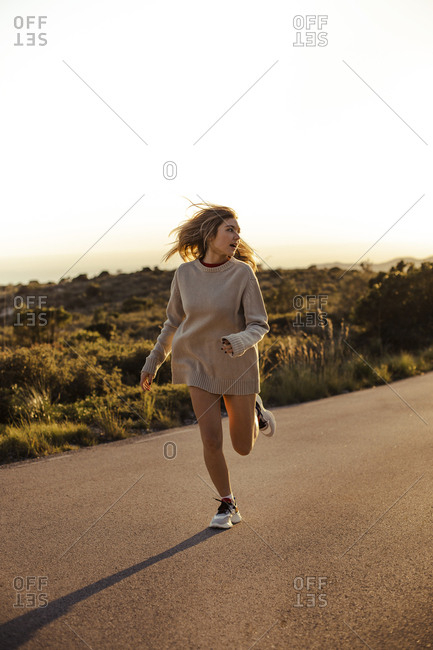 Pretty blond girl running and laughing on a road during the sunset in Barcelona
