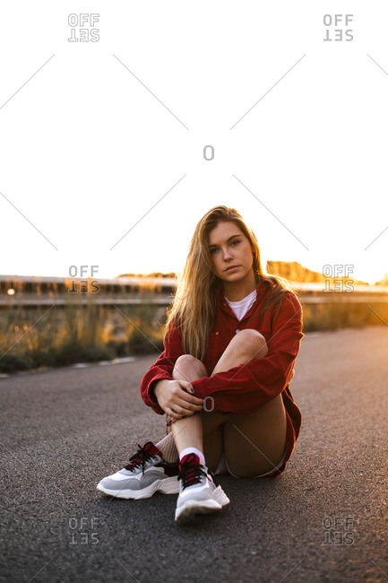 Portrait of a pretty blonde girl sitting on the road during sunset