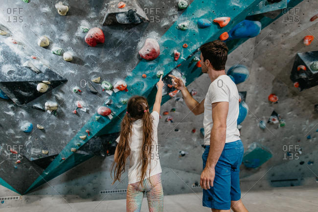 Back view of a young girl planning her way up a bouldering wall with an instructor. Bouldering coach with a child pointing at boulders in an indoor bouldering gym.