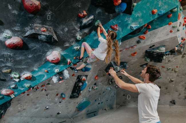 Young girl making her way up an artificial climbing wall with an instructor spotting. Child learning to climb up a bouldering wall with a coach in an indoor bouldering gym.