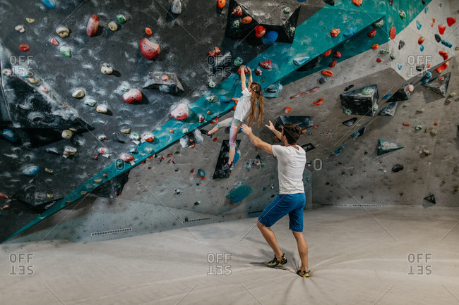 Back view of a bouldering instructor catching a child hanging from a climbing wall. Child learning to climb up a bouldering wall with a coach in an indoor bouldering gym.