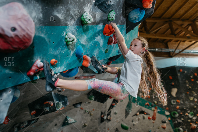 Portrait of a young girl enjoying climbing in an indoor bouldering gym. Child learning to climb up an artificial climbing wall.