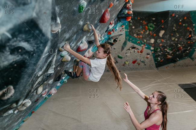 Female bouldering trainer helping a child climb up an artificial climbing wall. Child learning to climb up a bouldering wall with a coach in an indoor bouldering gym.