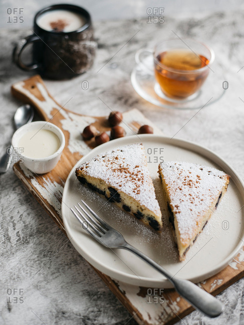 Cake covered in icing powder and cut into pieces with cup of tea