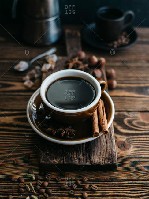 A cup of black coffee and coffee beans on wooden table