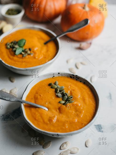 Homemade pumpkin soup with pumpkin seeds served in ceramic bowl