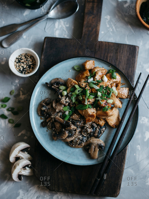 Chicken stir fry with roasted mushrooms and onion served on ceramic plate with wooden chopsticks