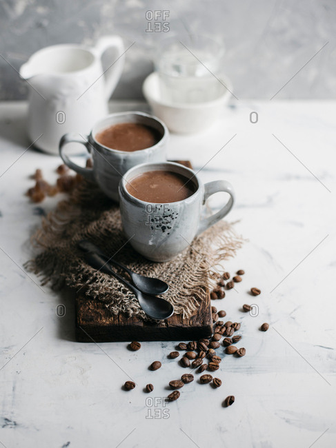 Mug of delicious hot cocoa and coffee beans on the table