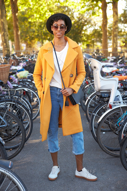 Full length vertical shot of a fashionable young woman wearing a hat and sunglasses, blue jeans and an unbuttoned yellow pea coat standing amongst parked bicycles