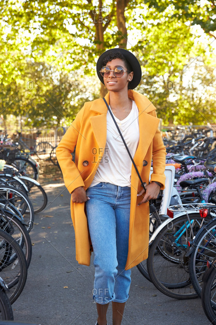 Fashionable young woman wearing a hat, sunglasses, an unbuttoned yellow pea coat and jeans walking amongst parked bicycles smiling, close up