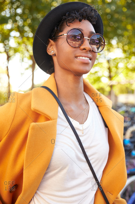 Fashionable young woman wearing a hat, sunglasses and an unbuttoned yellow pea coat walking in a city street smiling, close up