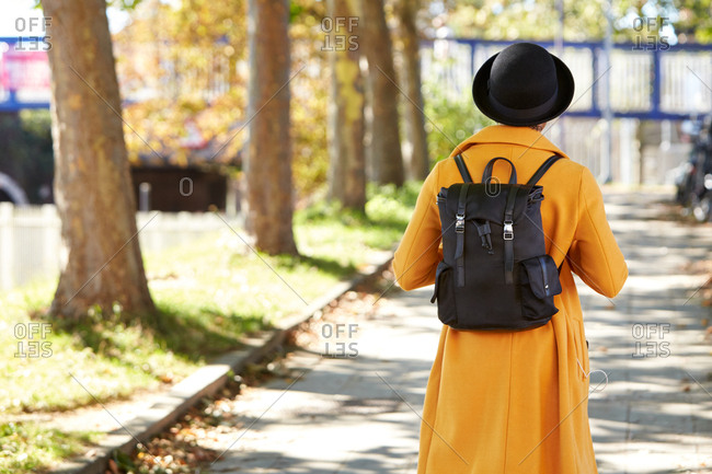Back view of a fashionable woman wearing a yellow coat and a black backpack walking on a tree lined city street, selective focus