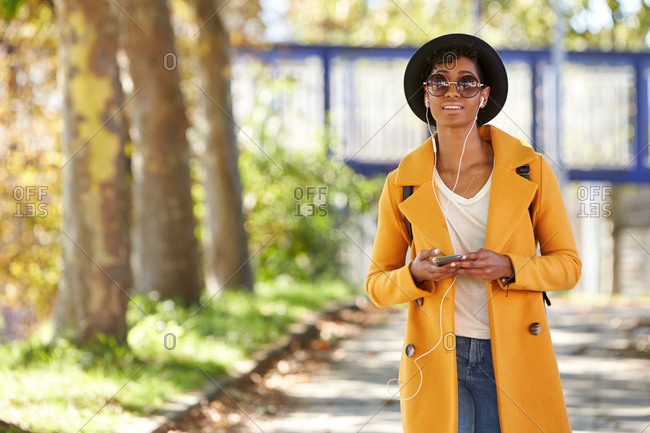 Fashionable young woman in a hat, sunglasses and an unbuttoned yellow pea coat walking along a tree lined street wearing earphones and holding her smartphone, selective focus