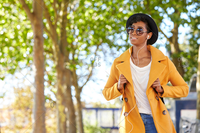 Fashionable young woman wearing a hat, sunglasses and an unbuttoned yellow pea coat walking on a tree lined street listening to music on earphones, close up